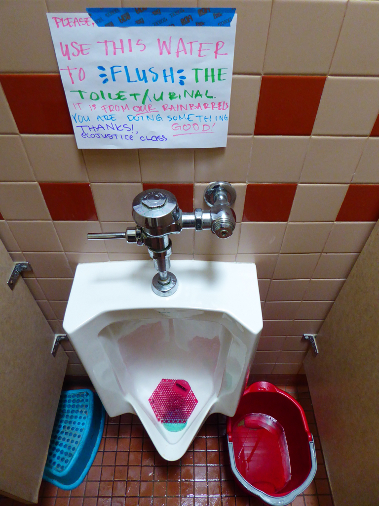 Photo showing a urinal at UUCPA with a partially empty bucket of rainwater next to it, and a sign saying to use the rainwater to flush the urinal