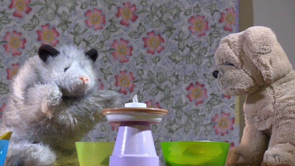 Video still showing Possum and Sharpie and a flaming chalice